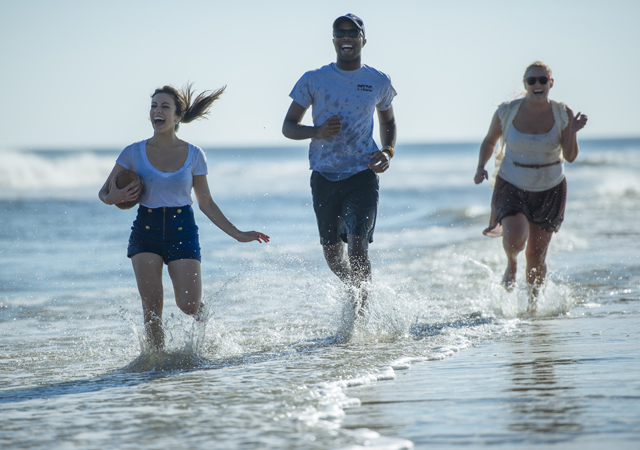 students running in water on the beach